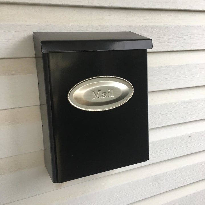 a reviewer photo of the black mailbox with a silver sign