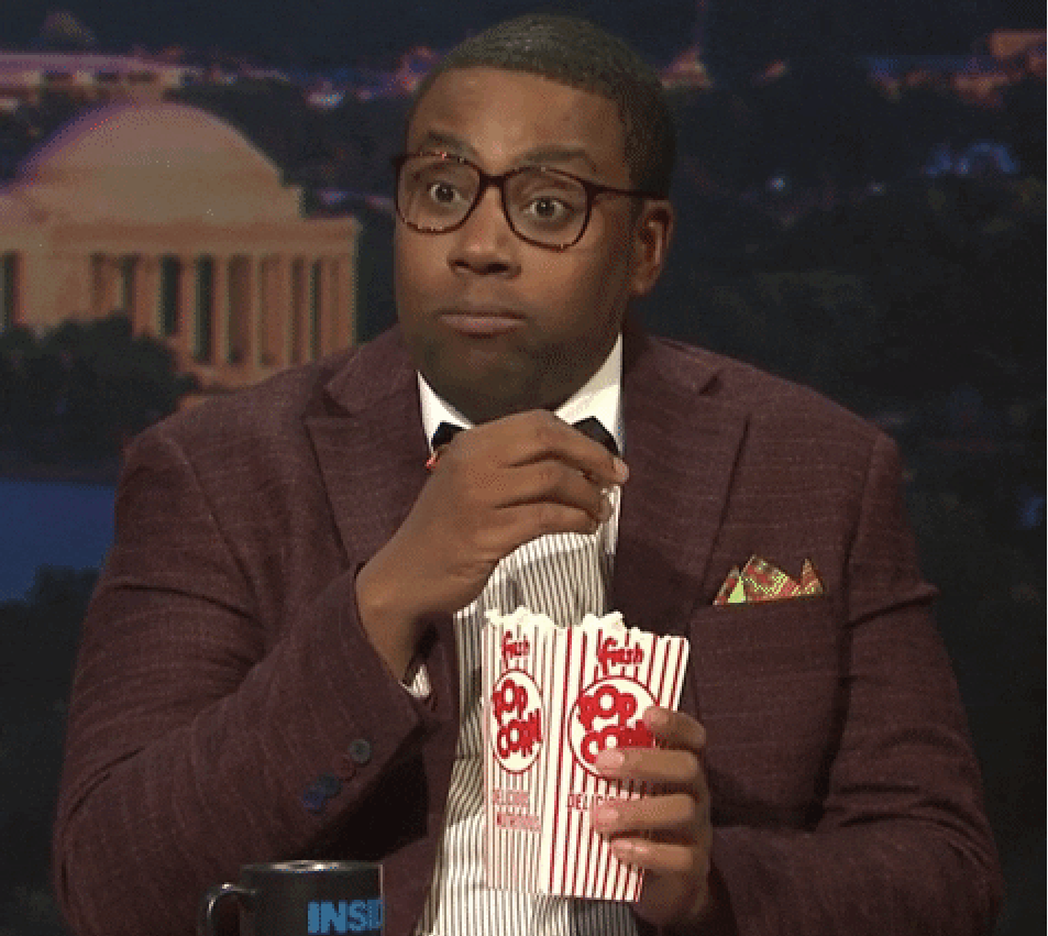 Kenan Thompson eating popcorn and looking engaged