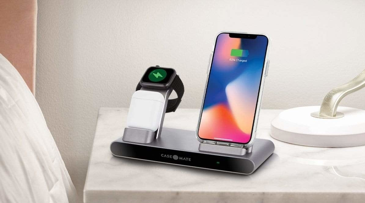 a phone, watch, and airpods on the charging base