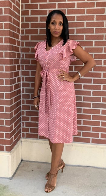 A reviewer wearing the V-neck, short-sleeve dress in pink. It hits just below the knee