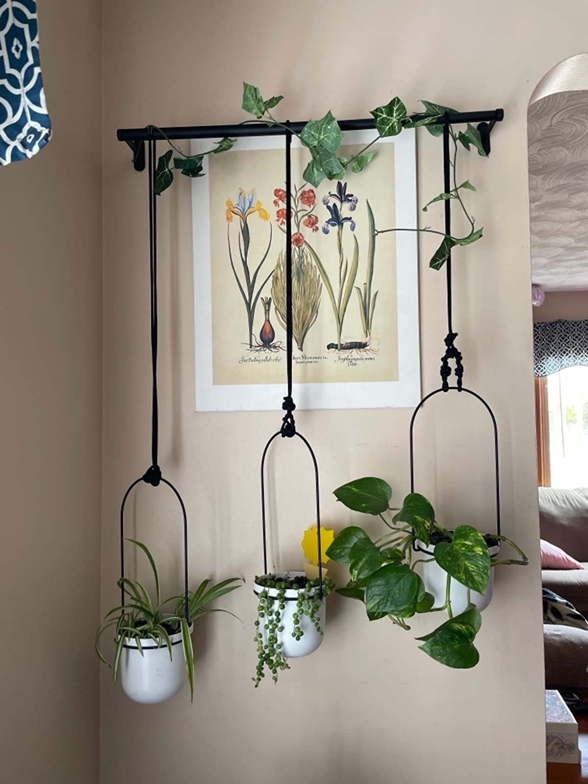 The planter mounted to a wall with three pots hanging down at various lengths