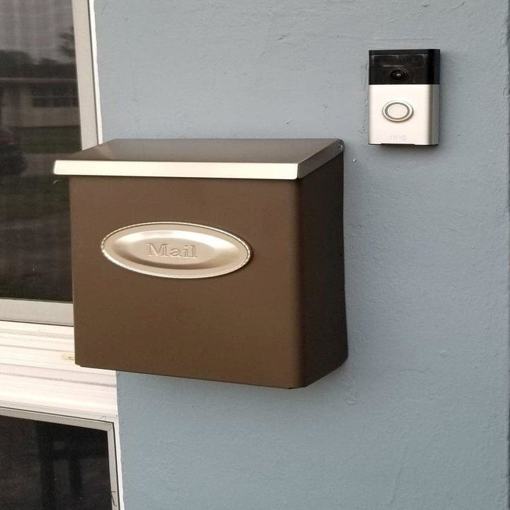 a reviewer photo of the mounted mailbox in brown with a silver lid and plaquee