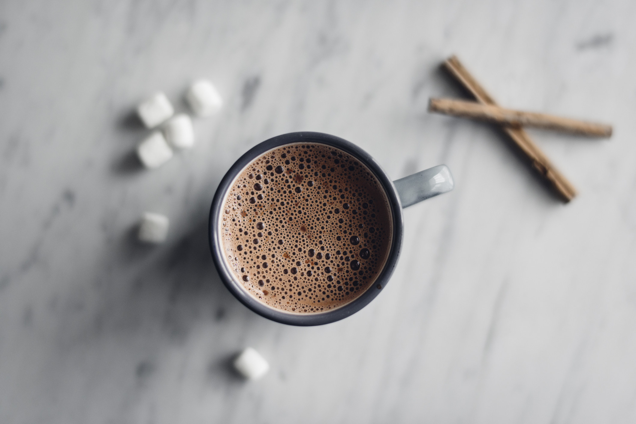 A mug of hot chocolate surrounded by marshmallows.