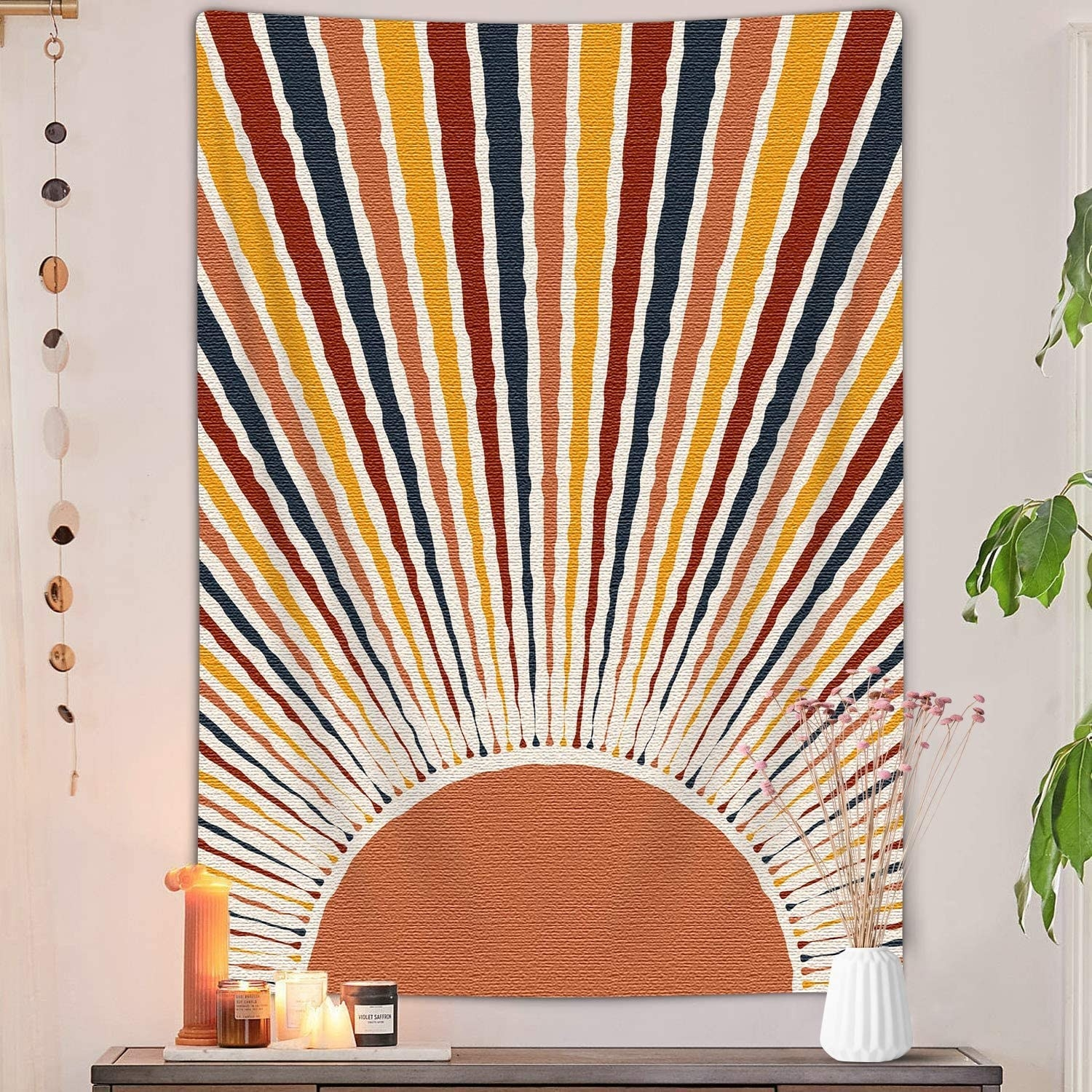 a tapestry hung on a wall with a sun and rays painted onto it
