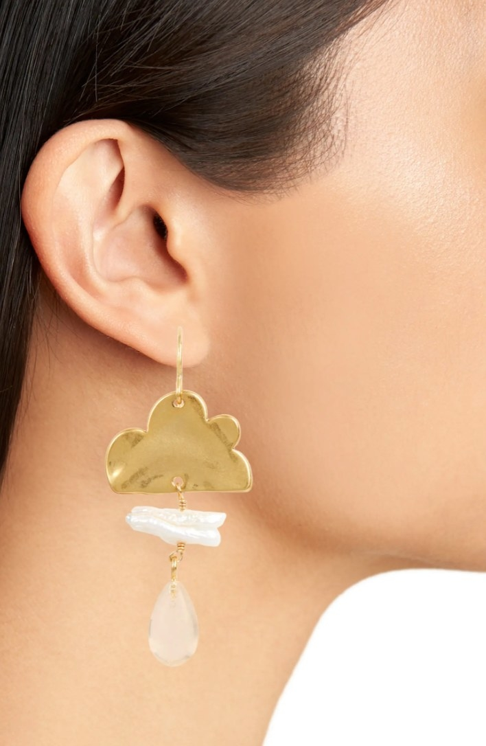 The pair of genuine pearl cloudcover earrings on a model