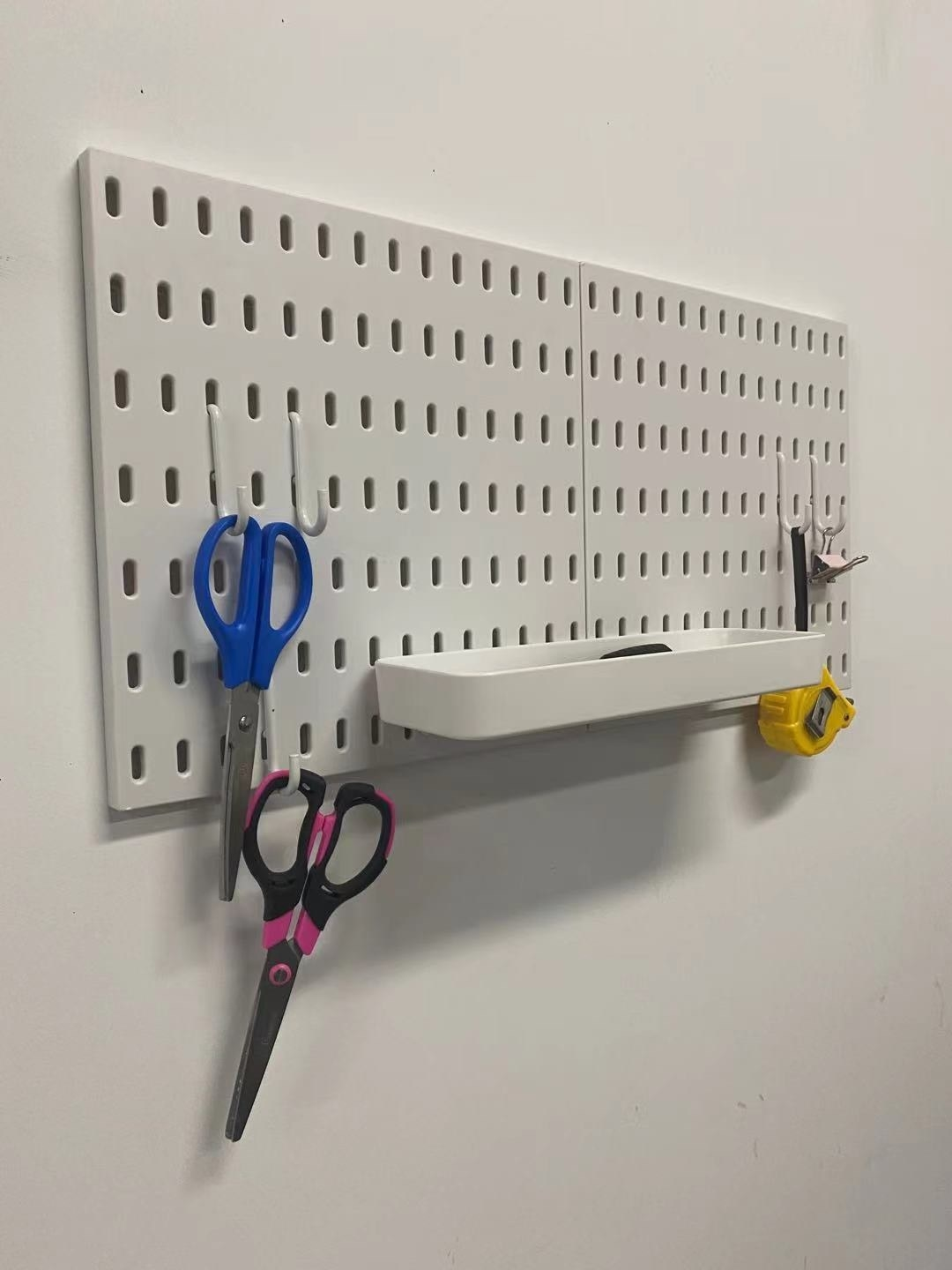 The pegboard with a shelf and several hooks holding items