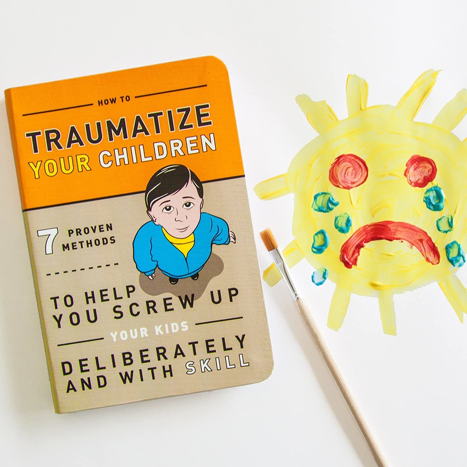 The cover of How to Traumatize Your Children next to a child-like painting of a sad sun