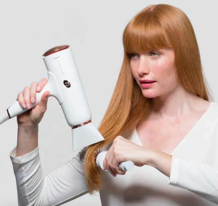A model blow-drying her hair with the T3 Cura Luxe Professional Ionic hair dryer