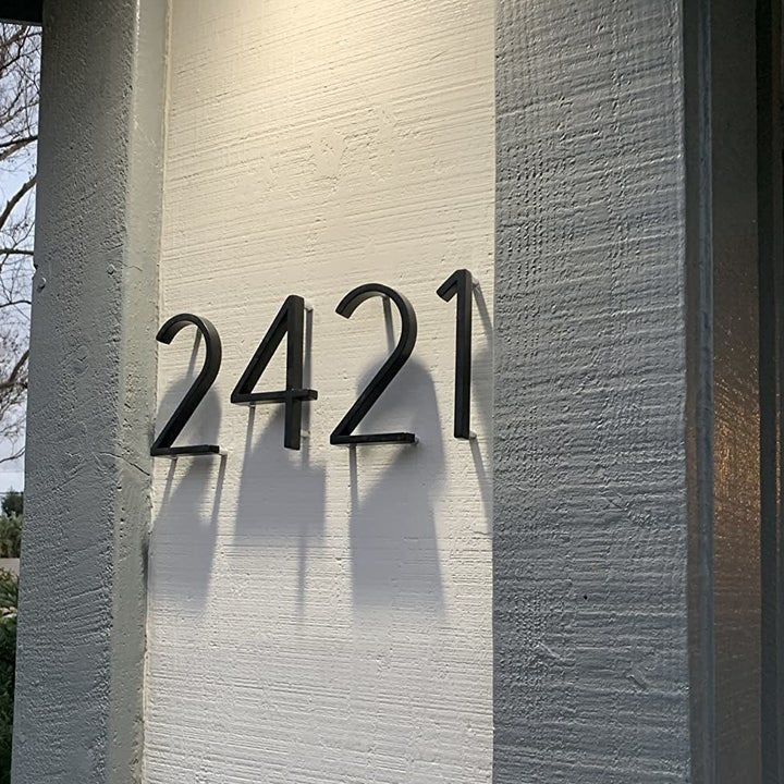 a reviewer photo of the black numbers 2,4,2,1 mounted on the wall