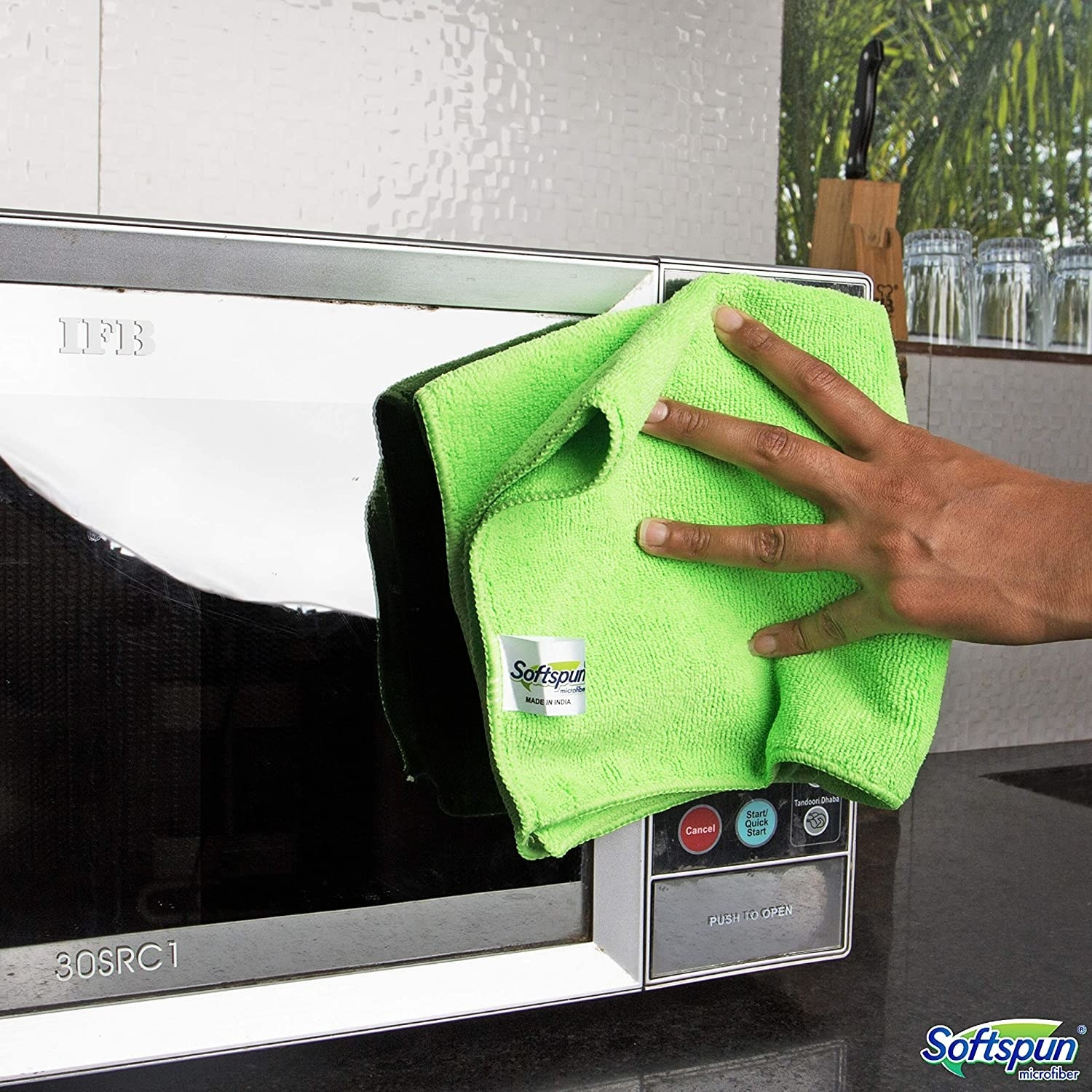A lime green microfibre cloth being used to clean a microwave door