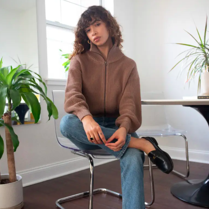 A model wearing the cardigan in clay
