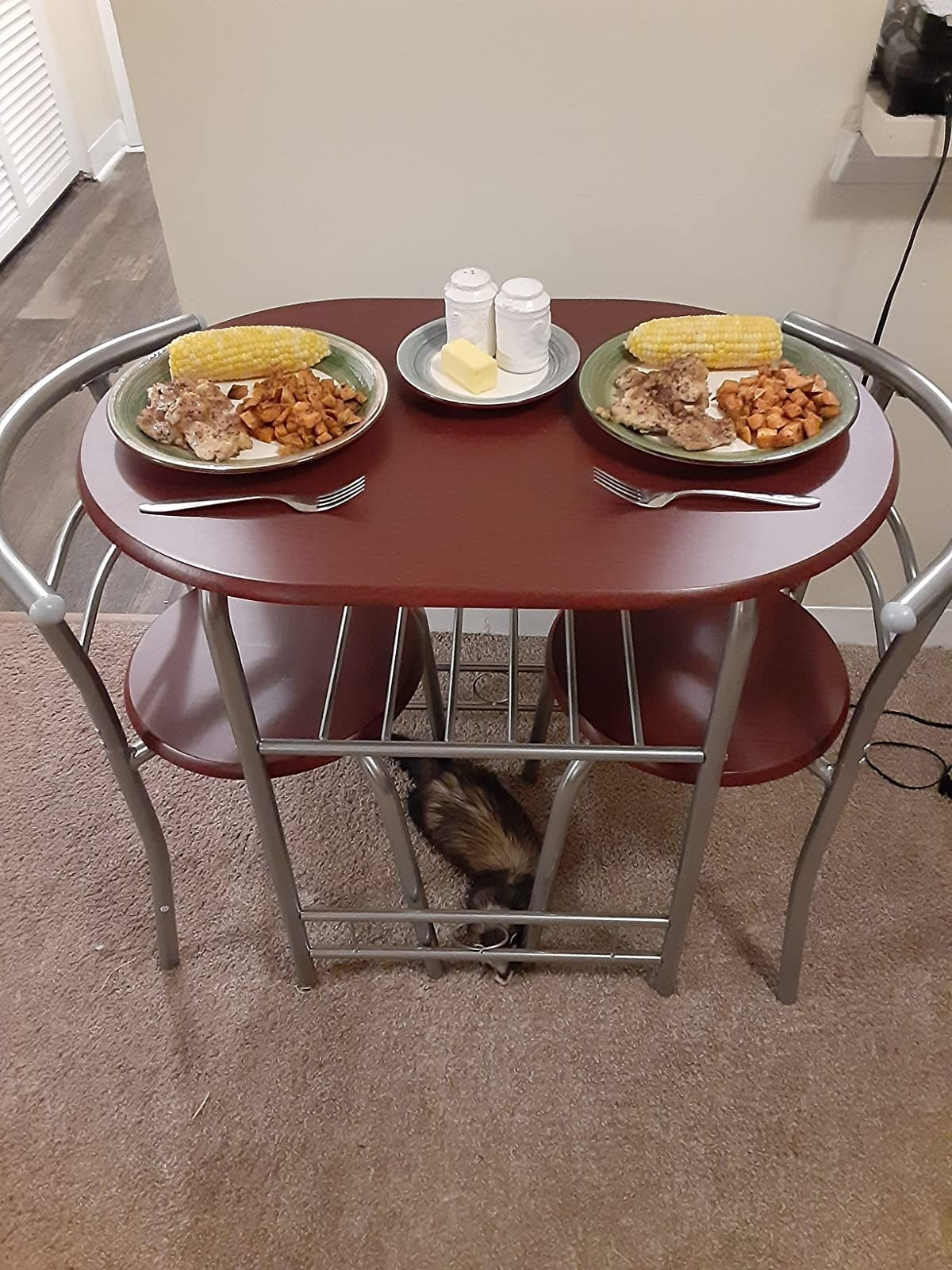The round dining table with two chairs that fit just underneath it