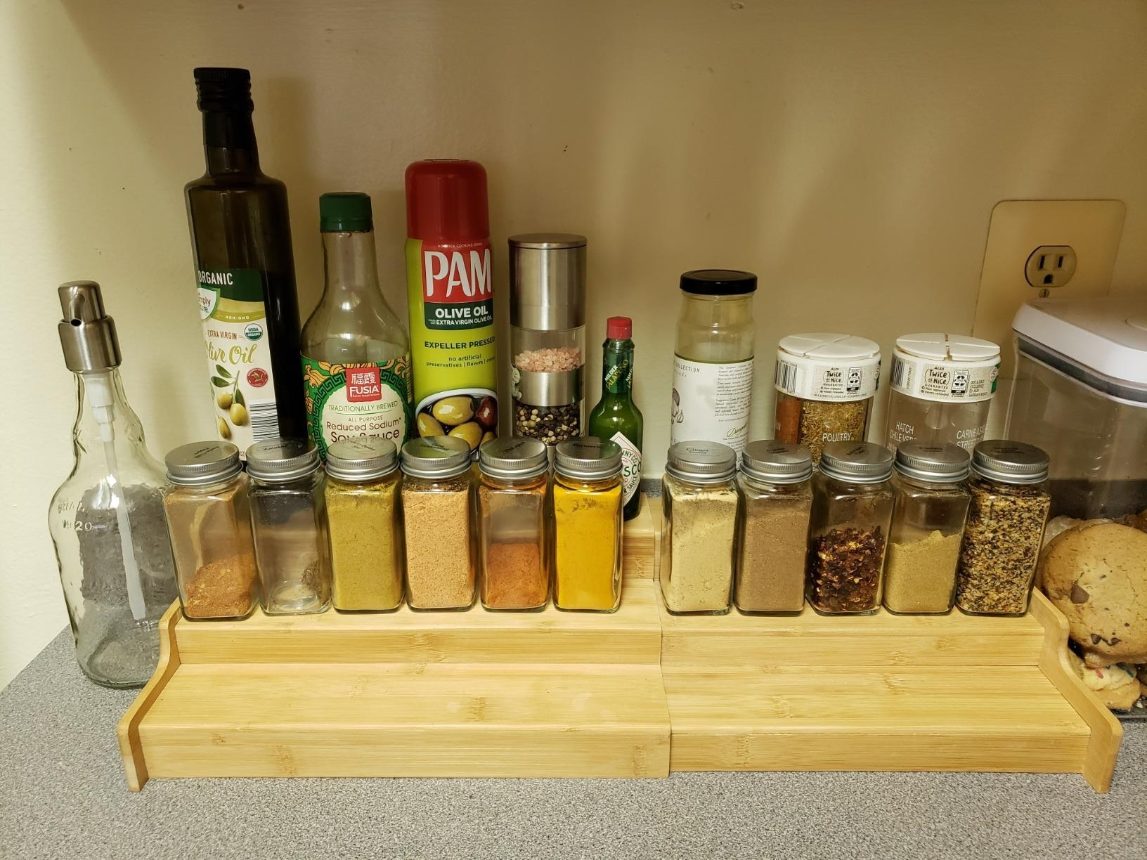 The spice rack with three tiers and several spices on each tiers