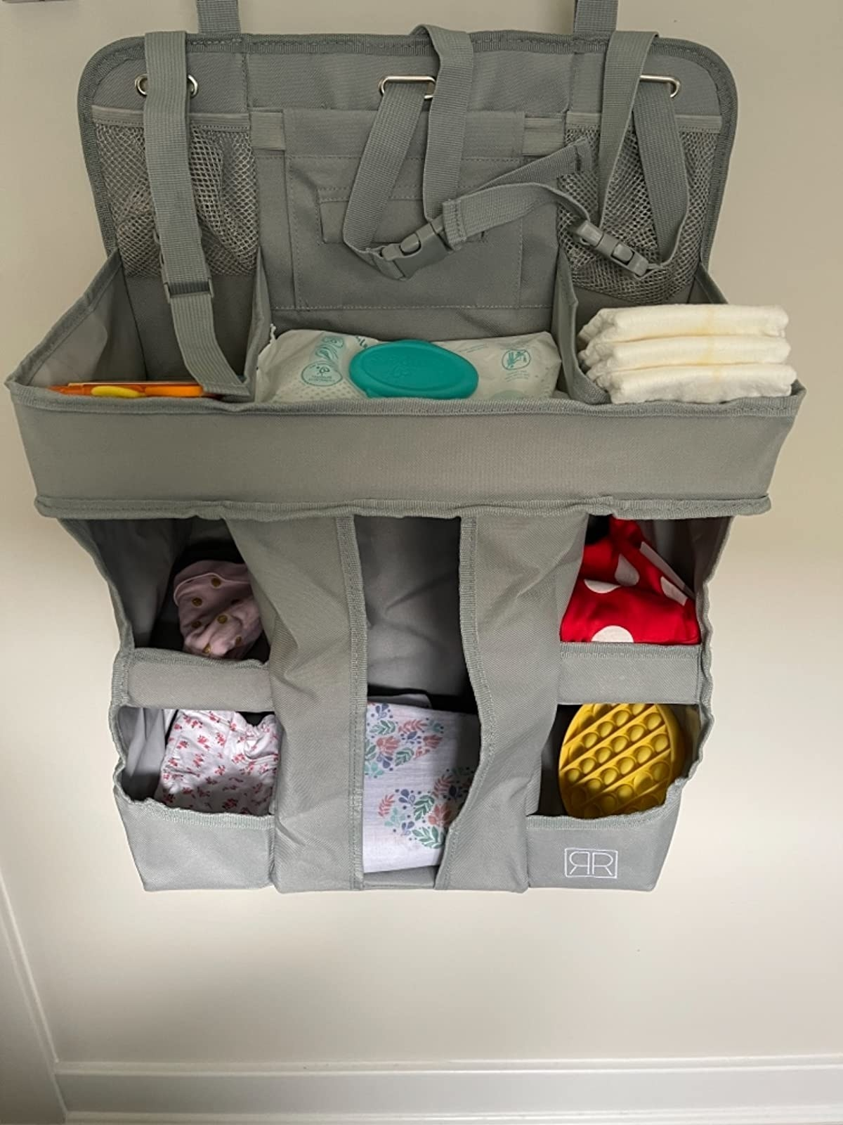 The organizer fastened to a wall holding diapers, wipes and more
