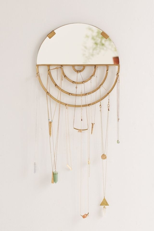 small gold circular mirror with pegs for jewelry on the bottom
