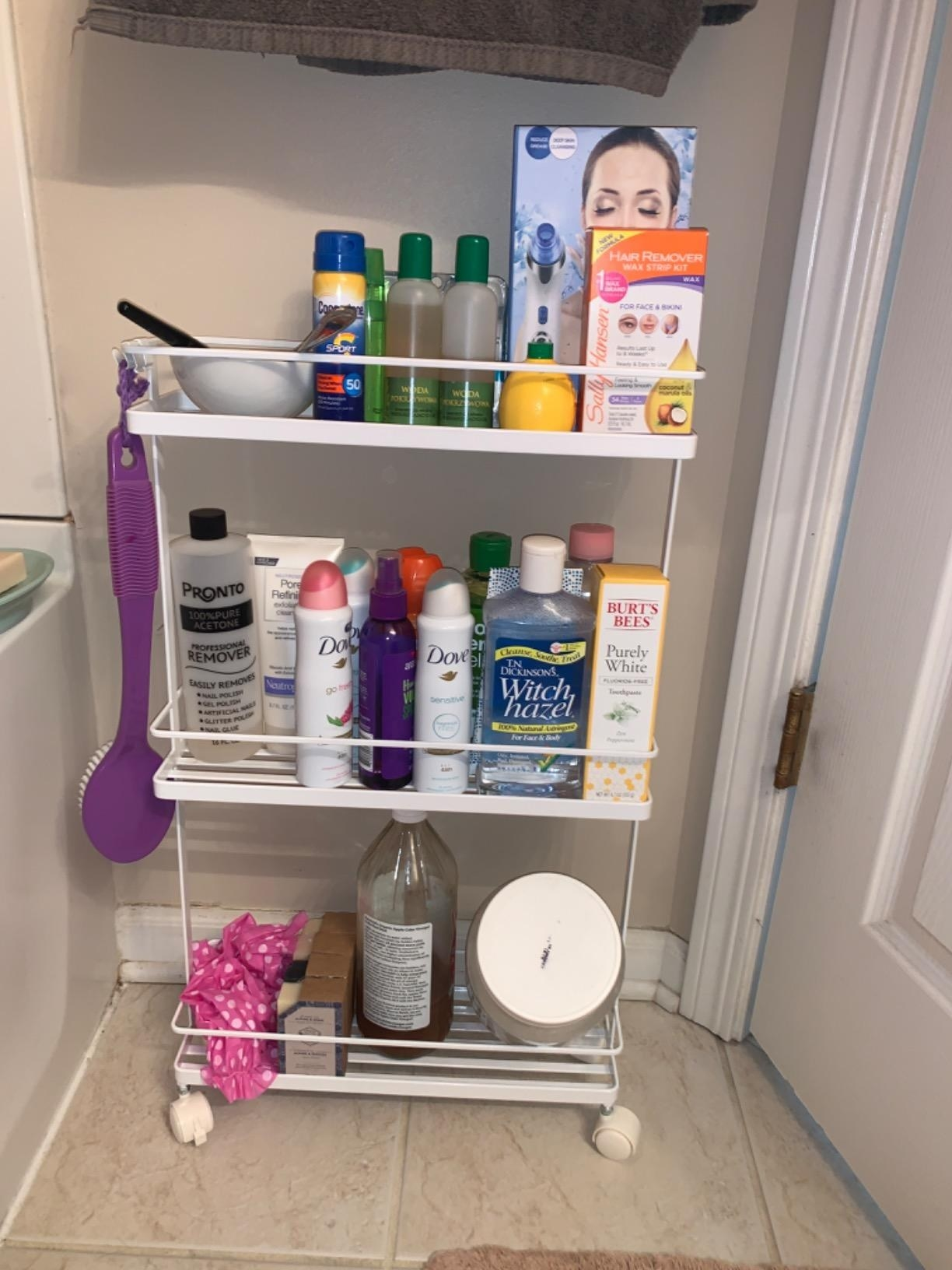 The narrow storage cart on wheels with three shelves holding bathroom essentials