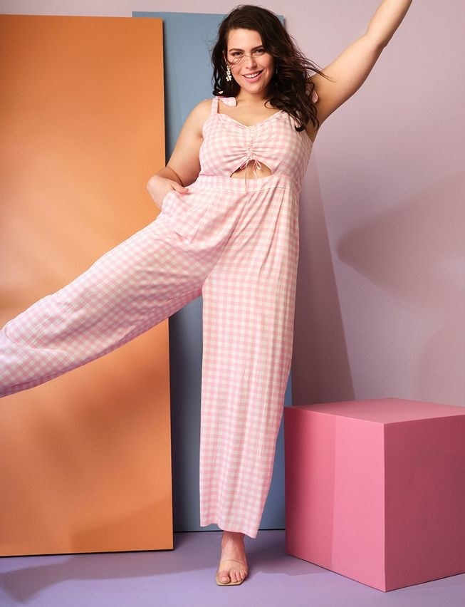 model in sleeveless wide leg pink and white jumpsuit with ruching at bust and with their hand in one of the pockets