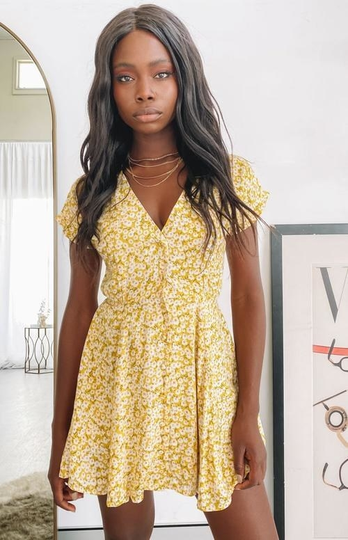 model in yellow floral mini dress with short sleeves and buttons