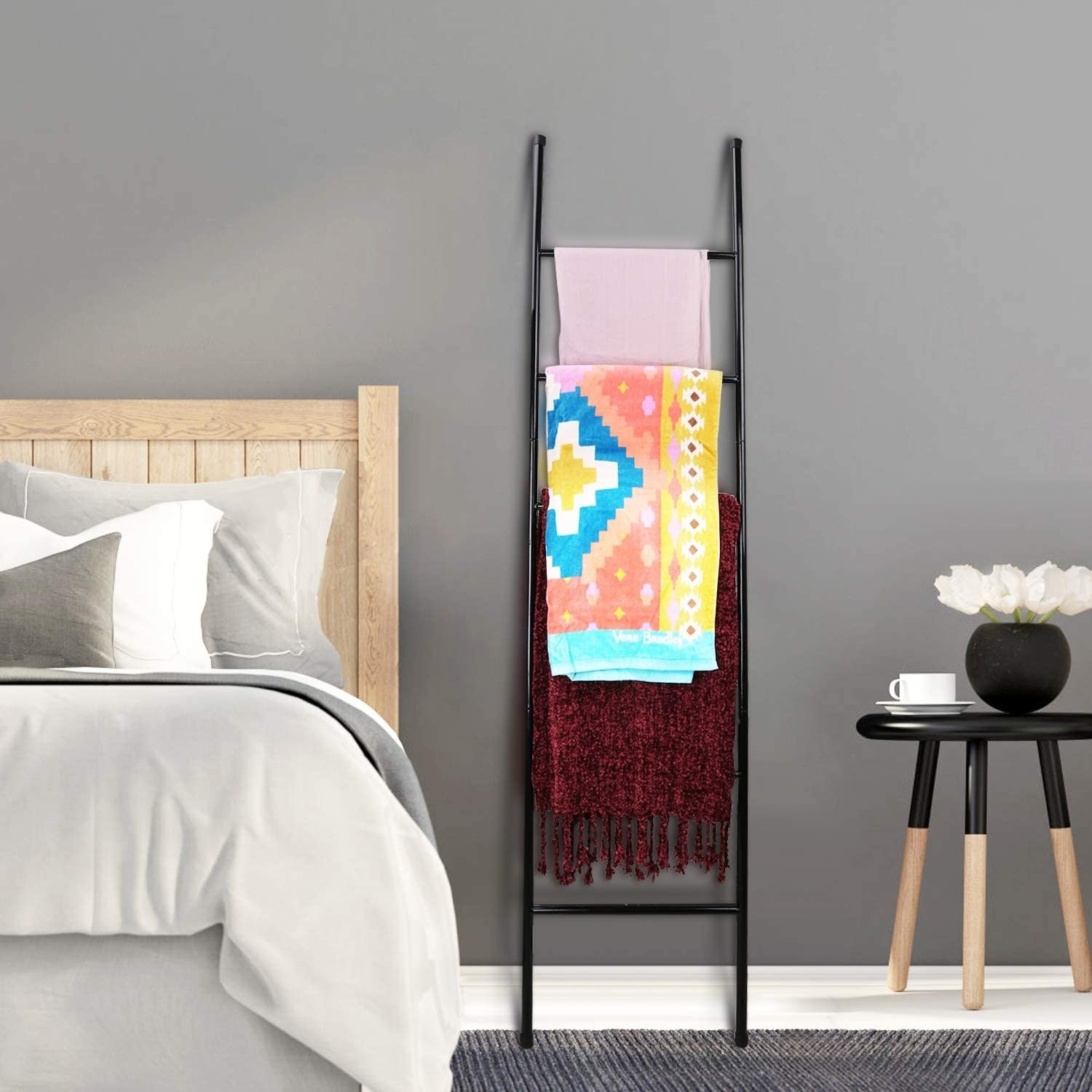 Display ladder with folded blankets and scarves next to a bed