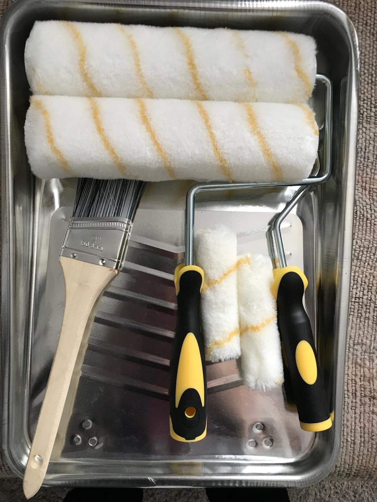 a reviewer photo of a silver paint tray filled with two large and two small roller brushes and a wooden paint brush