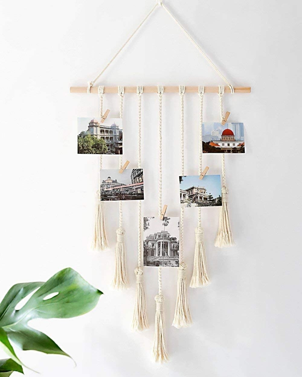 White hanging photo organizer with clips for postcards, photos, and notes above a desk