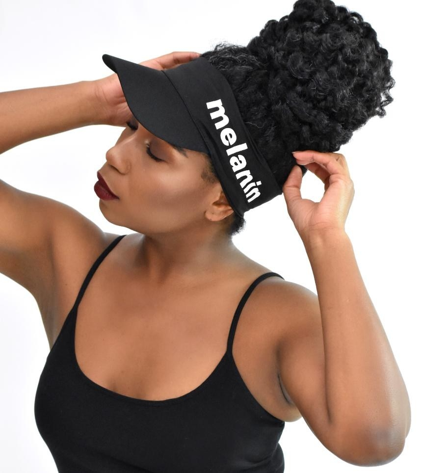 A person wearing the visor with their hair in a bun