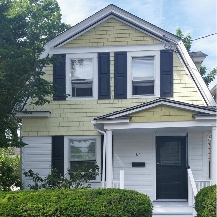 a reviewer photo of the same house with navy blue shutters on the windows