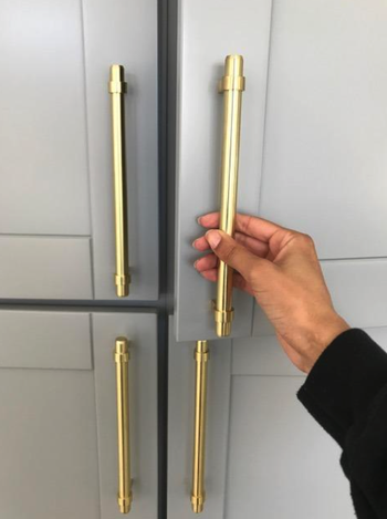 reviewer pulling gold pull on kitchen cabinet