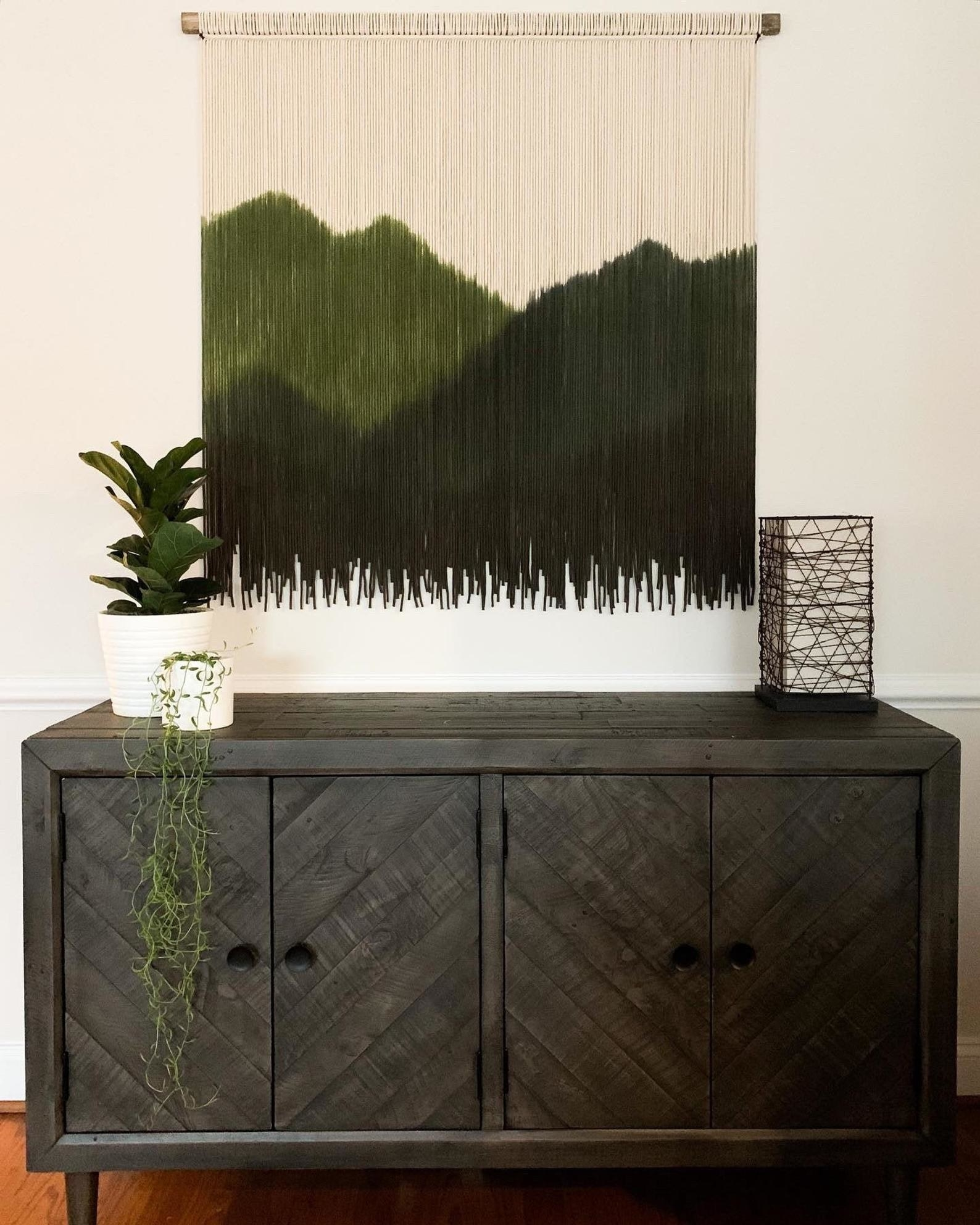 macrame tapestry hanging with different threads of green making up an outline of mountains