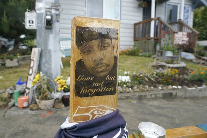 """A memorial featuring a photo of Manuel Ellis with the words """"Gone but not forgotten"""""""