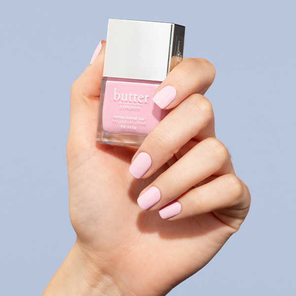 manicured hand holds bottle of pink nail polish