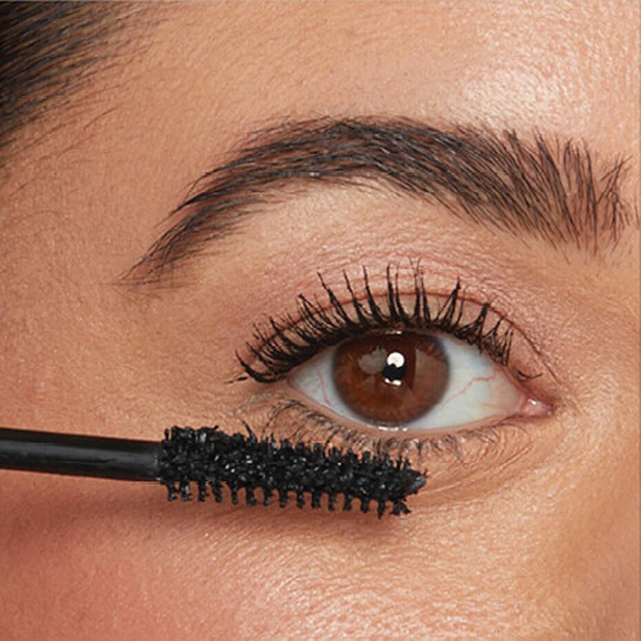 model uses spoolie to apply mascara onto lashes