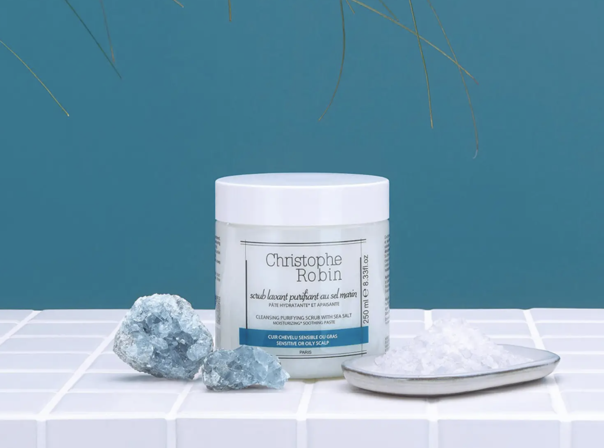 tub of skin cleansing scrub next to crystals