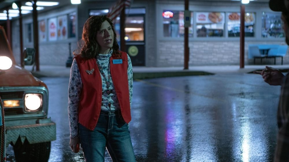 Edi Patterson as Doris standing outside the gas station at night