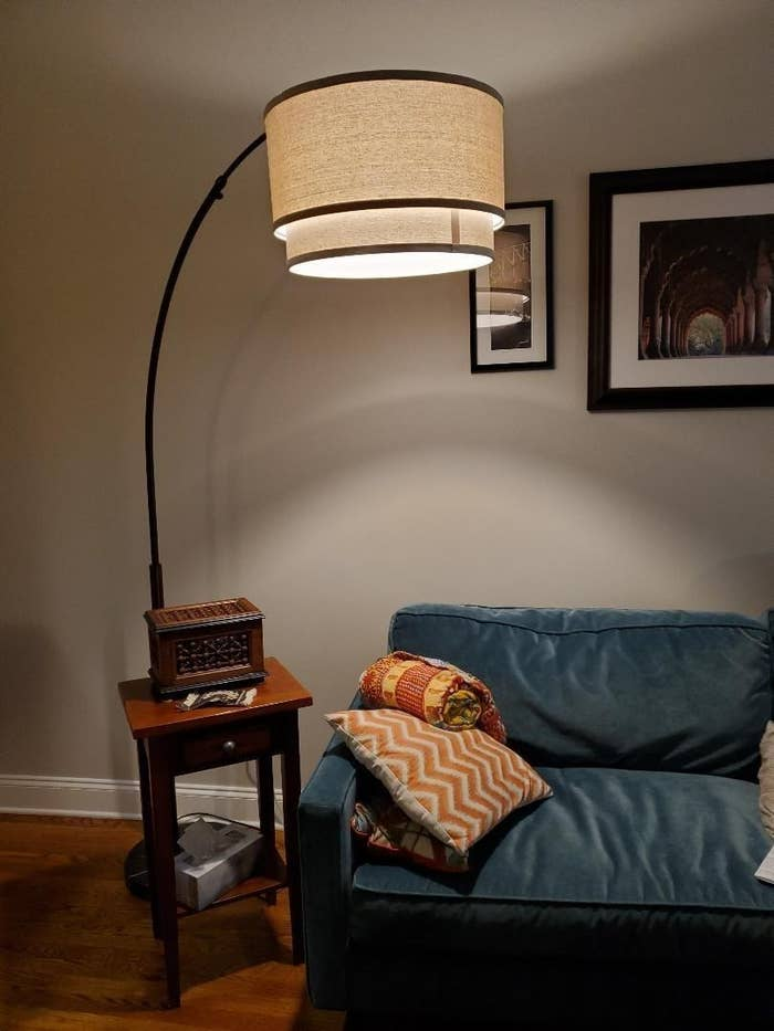 The arched lamp with a marble base and hanging drum shade in a living room
