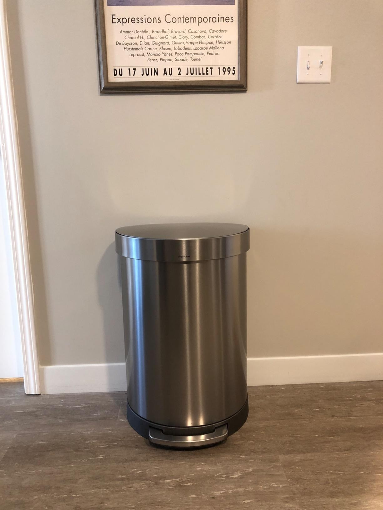 The semi-round trash can against a wall