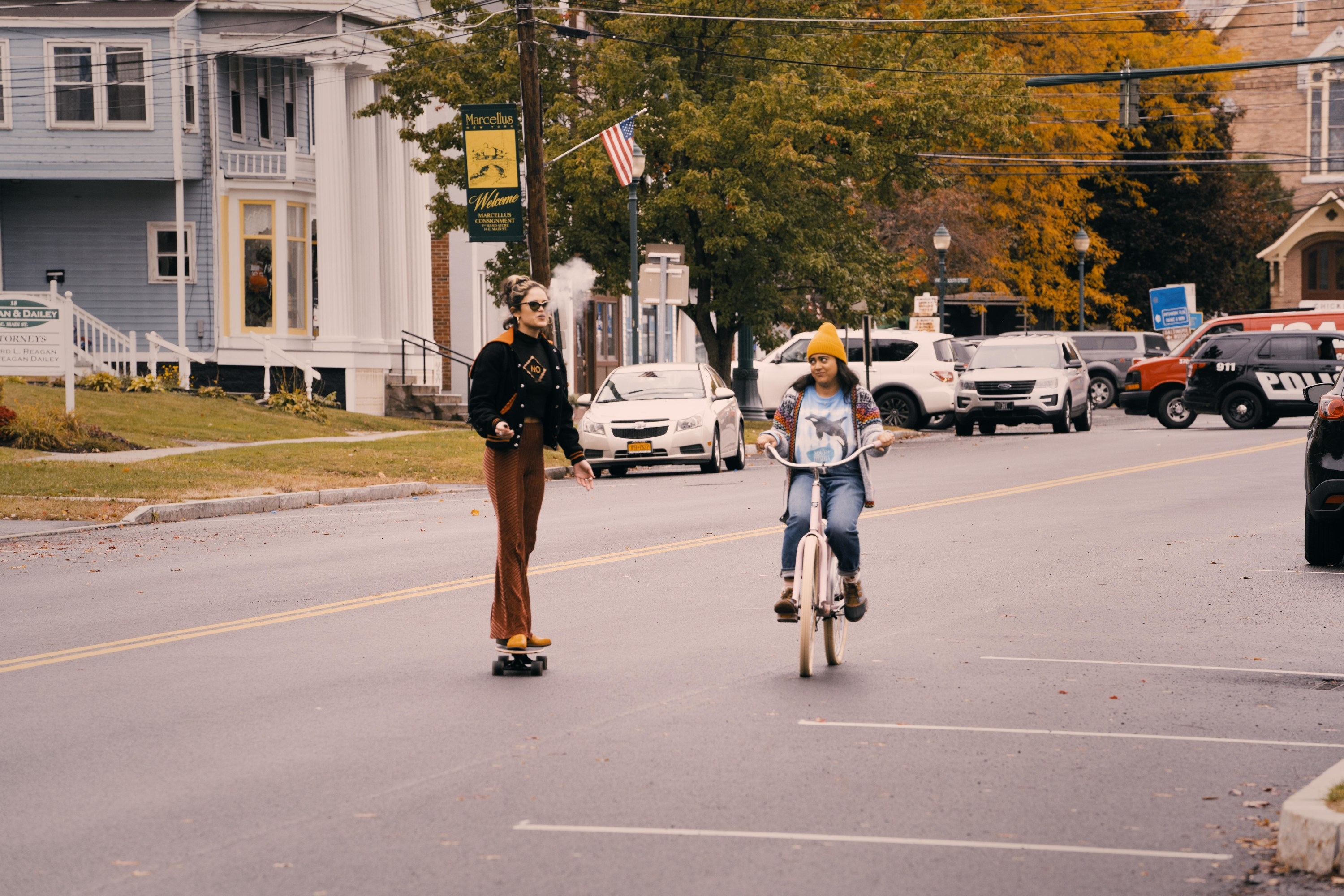 Lupe rides a skateboard while Sunny rides a bike through downtown in a small town