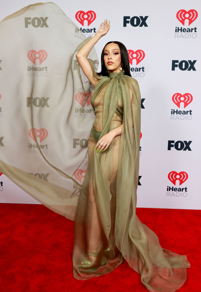 Doja Cat attends the 2021 iHeartRadio Music Awards in a see through dress with cape