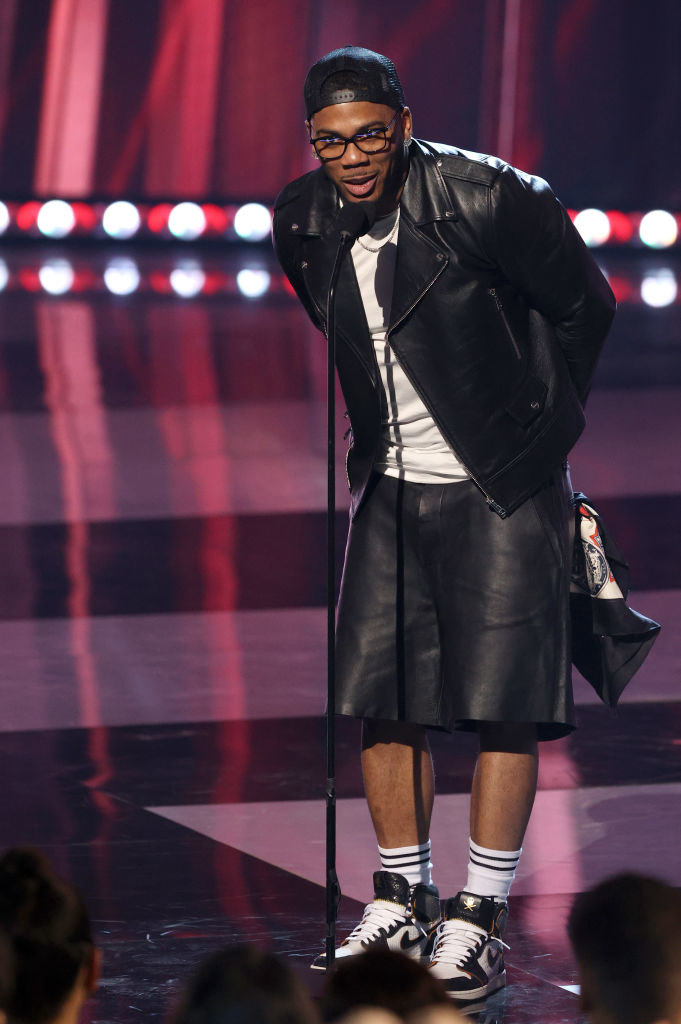 Nelly speaks onstage at the 2021 iHeartRadio Music Awards in leather shorts, a tee, and a leather jacket