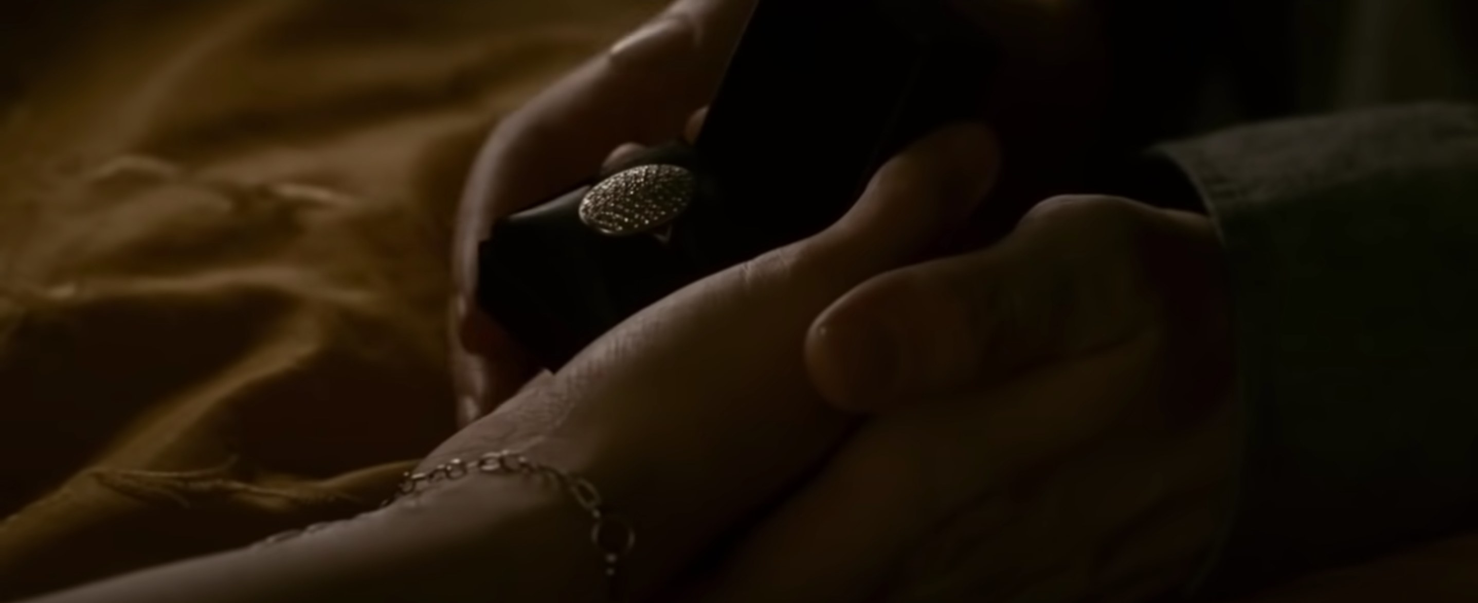 Edward putting a box with an engagement ring into bella's hand