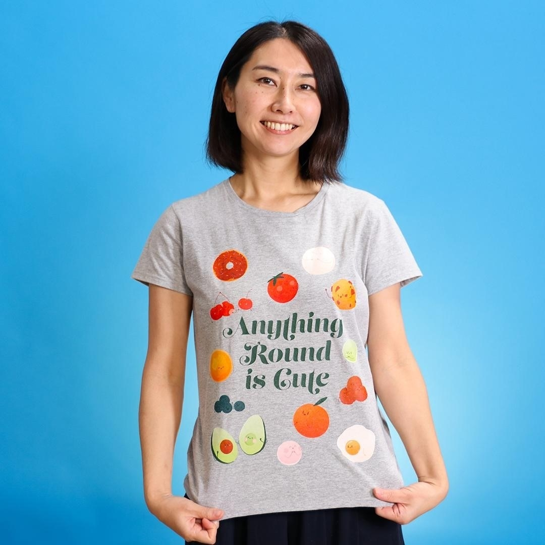 """grey t-shirt with illustrations of different food and the phrase """"Anything round is cute"""" on it"""