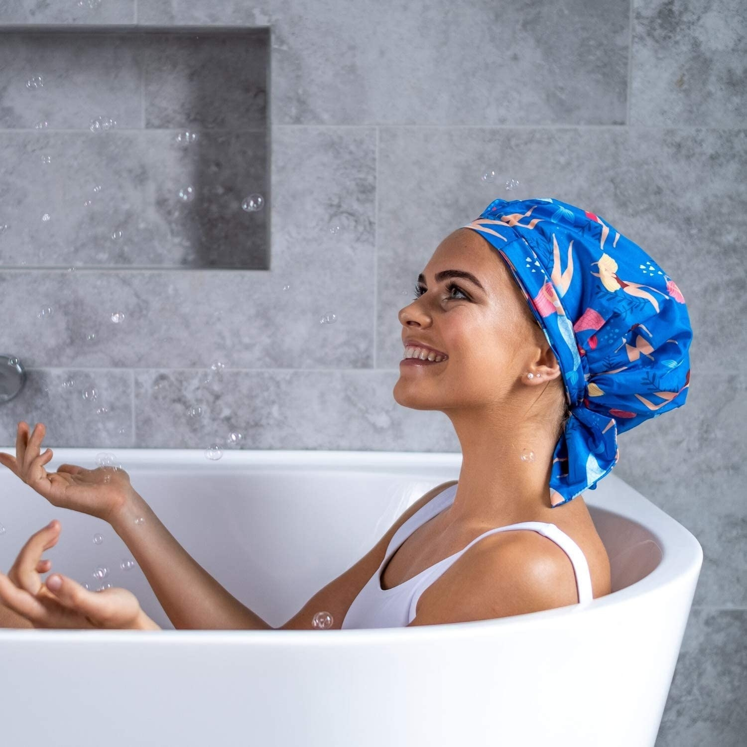 A smiling person wearing the shower cap in a bath tub.