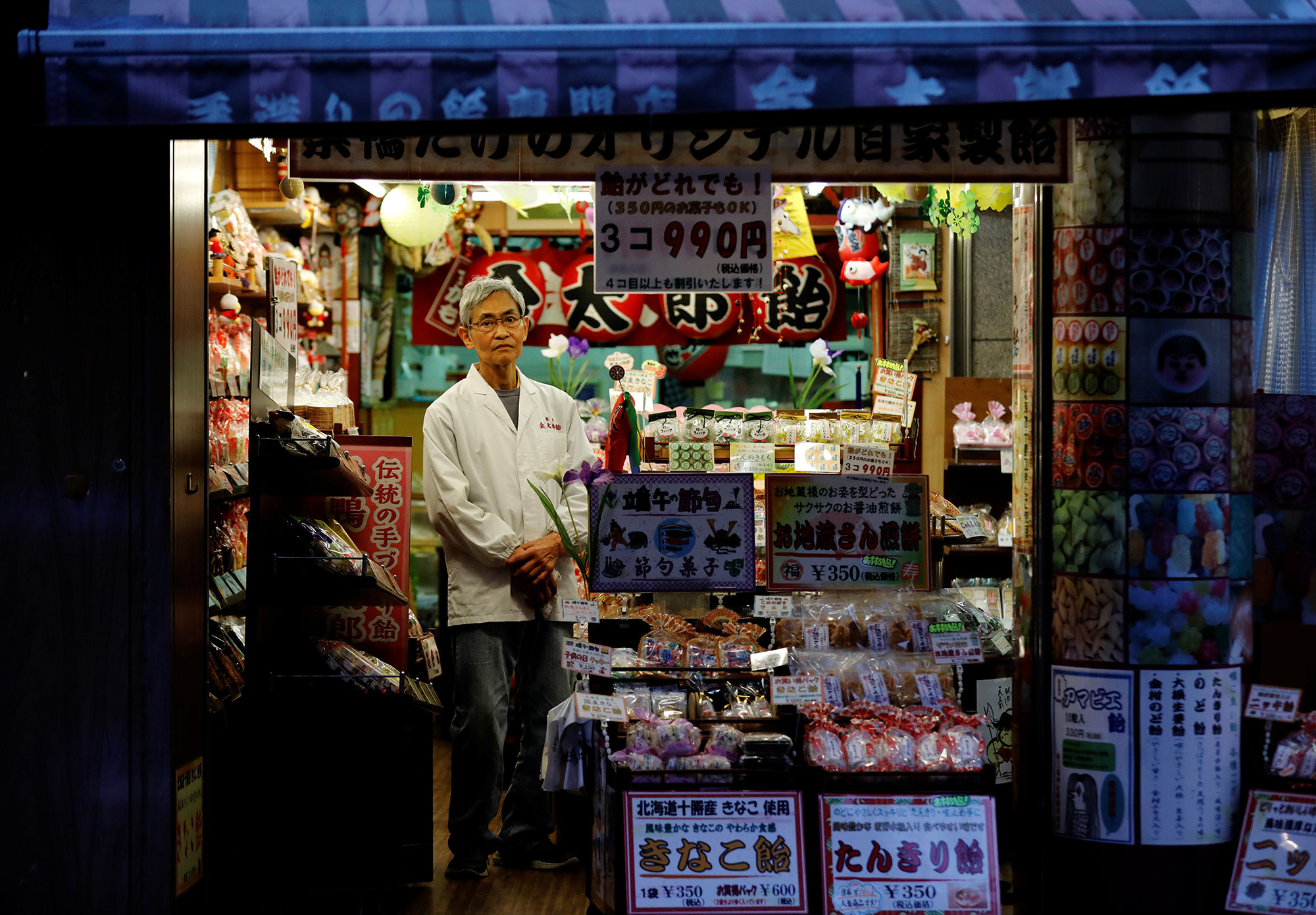 A man stands in front of a store as he holds his hands together