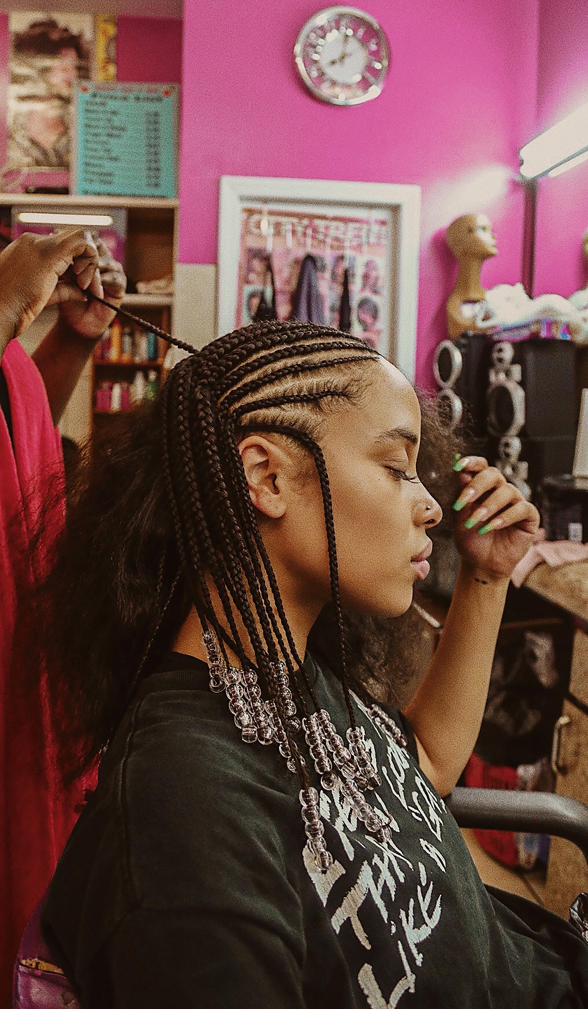 A woman sits while a hairdresser braids her hair