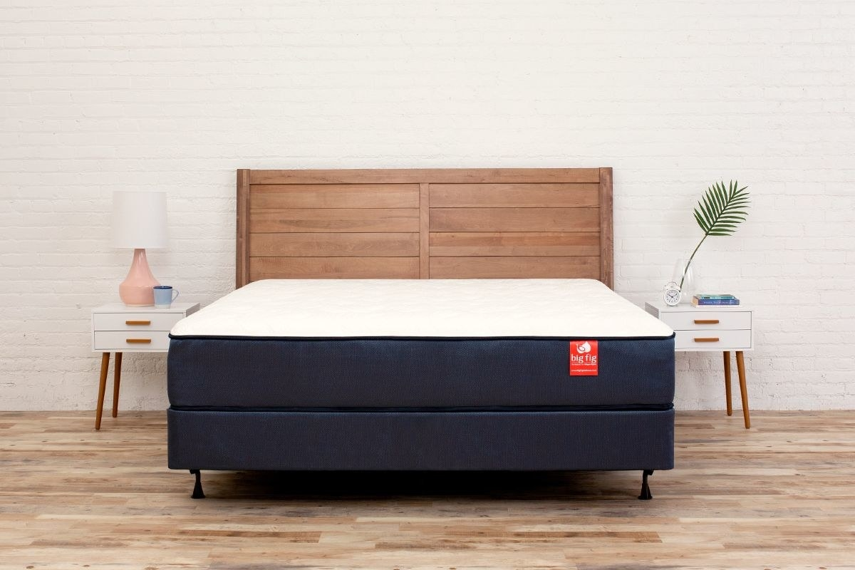 a navy and white mattress on a bed frame