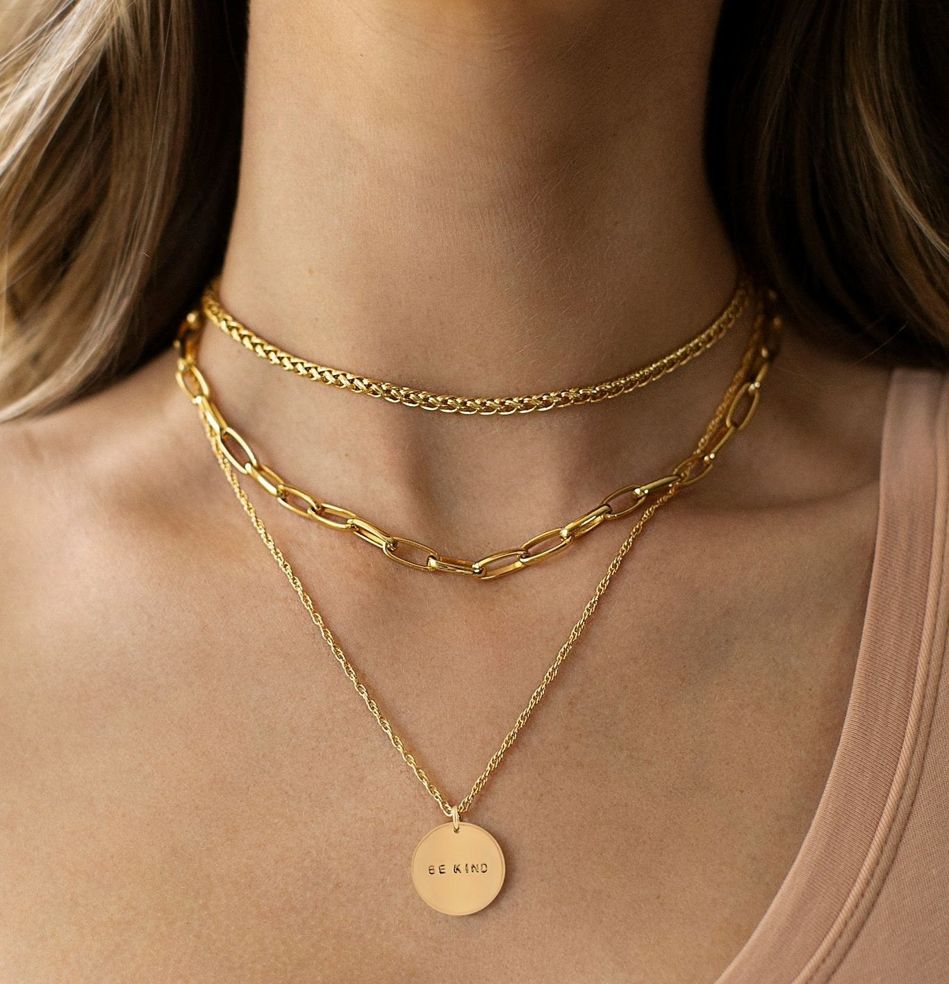 model wearing two chain and one pendant necklaces