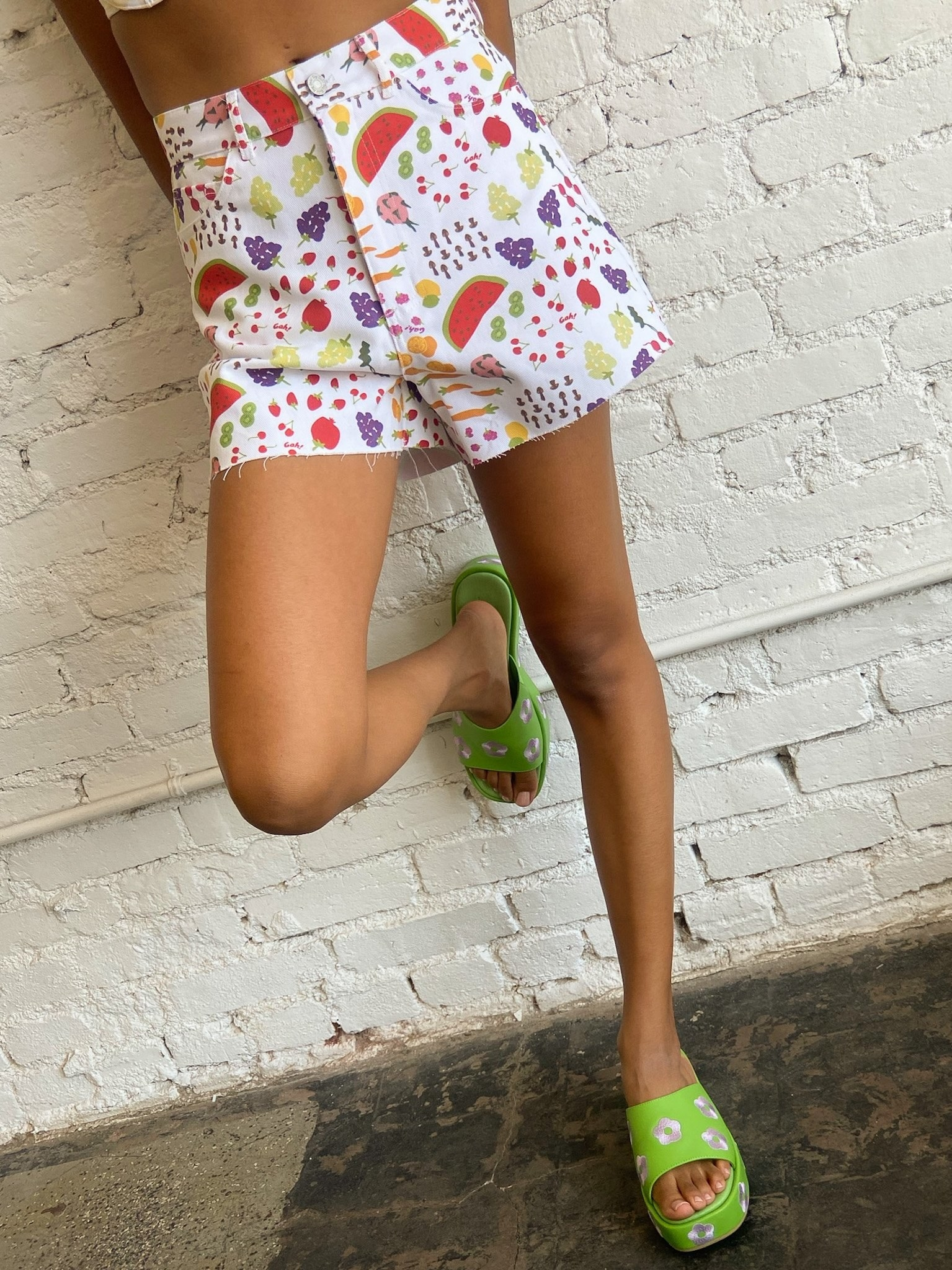 model wearing white demin shorts with illustrations of fruit all over them