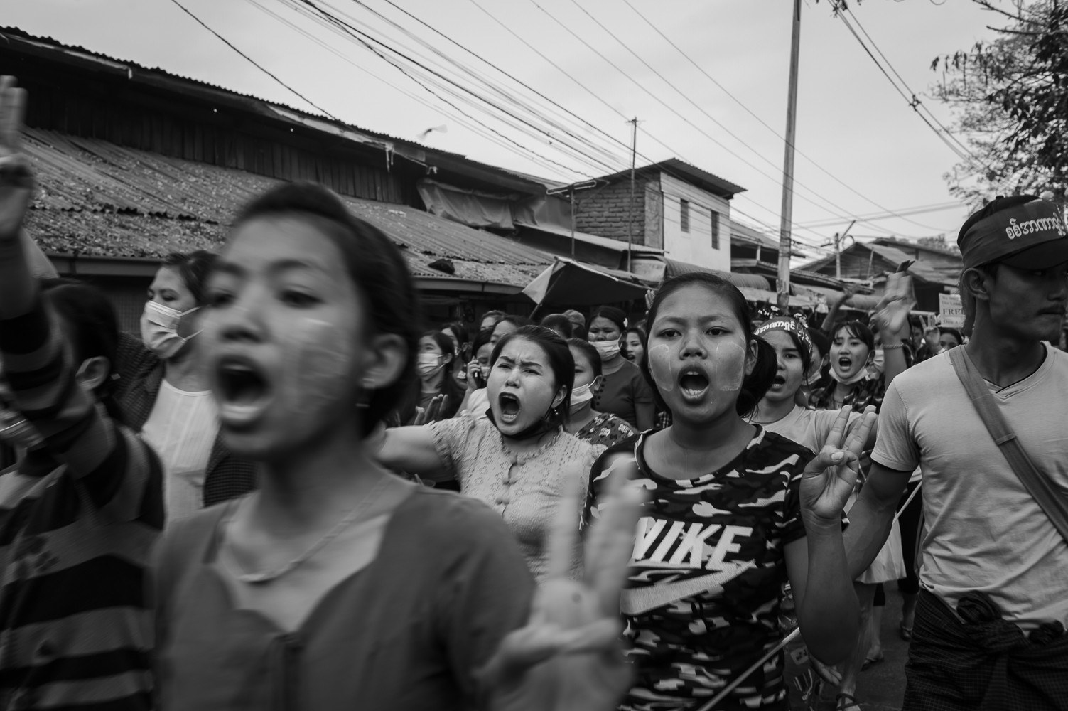 Women workers demonstrate against the coup, giving the three-finger salute in Insein Township on Feb. 18
