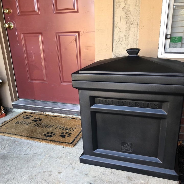a reviewer photo of the black delivery box on a front stoop by the door