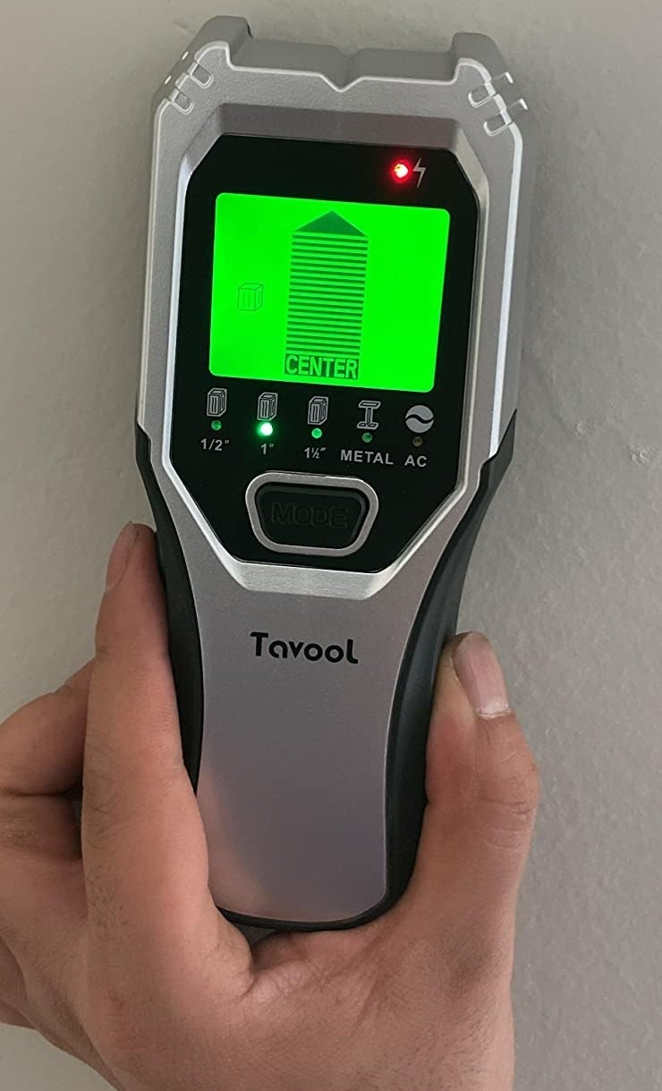 a reviewer photo of a hand using the stud finder with the screen indicated a stud has been found